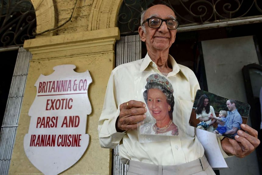 Boman Kohinoor, 93, poses with photos of Queen Elizabeth, and the Duke and Duchess of Cambridge outside his restaurant in Mumbai on April 8, 2016. The famous Parsi cafe, called Britannia & Company restaurant, opened in 1923.