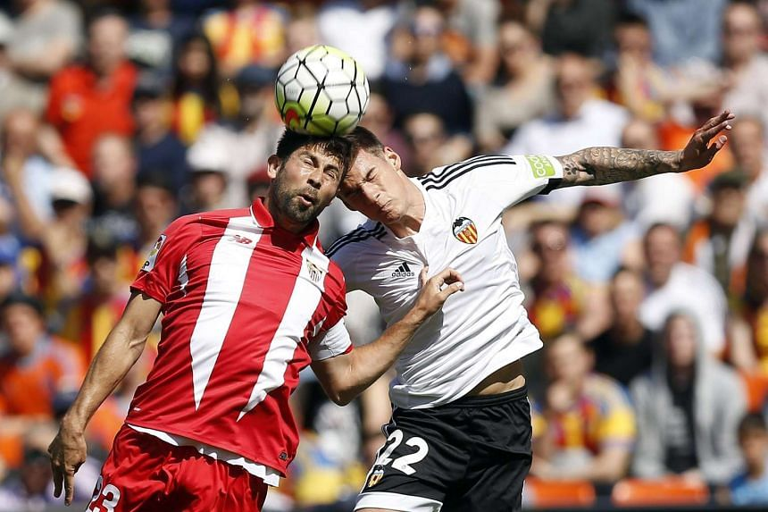 Valencia CF's forward Santi Mina (R) fights for the ball against Coke Andujar of Sevilla FC during their Spanish Primera Division League soccer match played at the Mestalla stadium in Valencia, eastern Spain, on April 10, 2016.