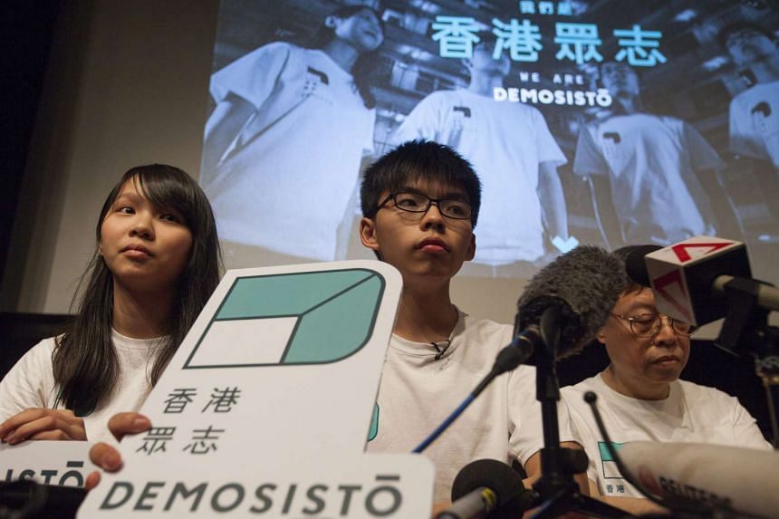 Agnes Chow (left), Deputy Secretary General of Demosisto, Joshua Wong (centre), Secretary General of Demosisto and Shu Kei (R) Ex-Committee Member of Demosisto, pose with the party logo at the launch of Demosisto, a new political party in Hong Kong,