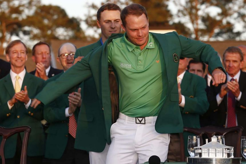Danny Willett (right) is helped into his green jacket by Jordan Spieth after winning the 2016 Masters Tournament at the Augusta National Golf Club.