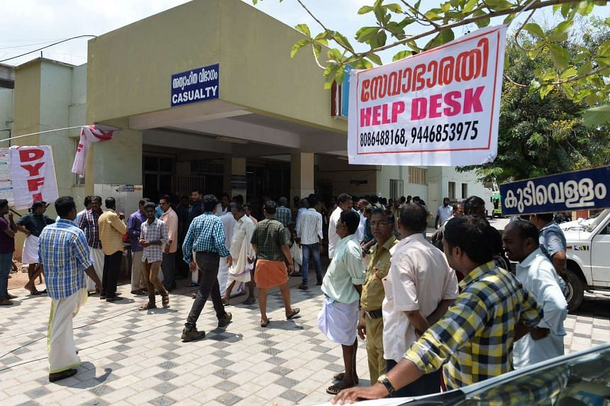 Relatives of injured or deceased victims of the Puttingal temple fire tragedy gather near a banner announcing a help desk in front of the casualty ward at Kollam District Hospital in Kollam on April 11, 2016.