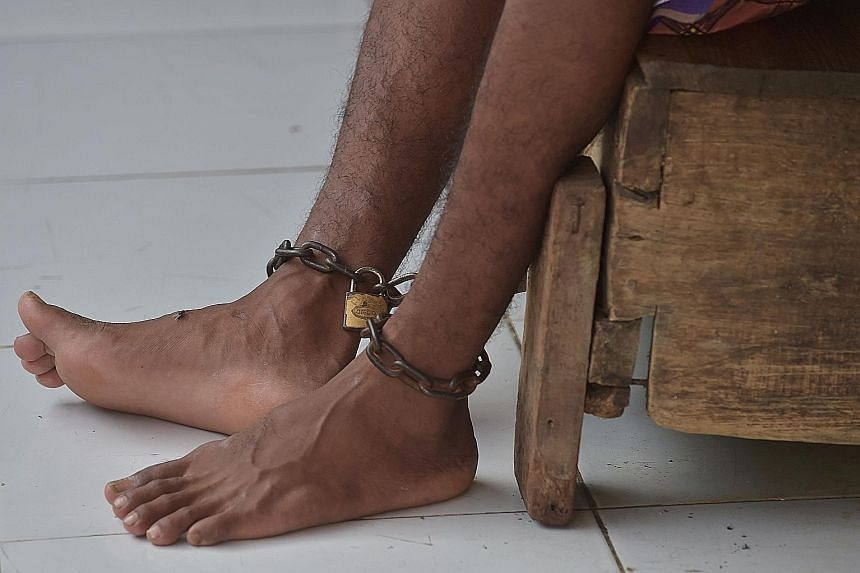 """A patient (above) with mental illness at Galuh Rehabilitation Centre in Bekasi. Over 18,000 Indonesians with mental illness are either shackled (left) or locked up in a confined space, a practice known as """"pasung""""."""