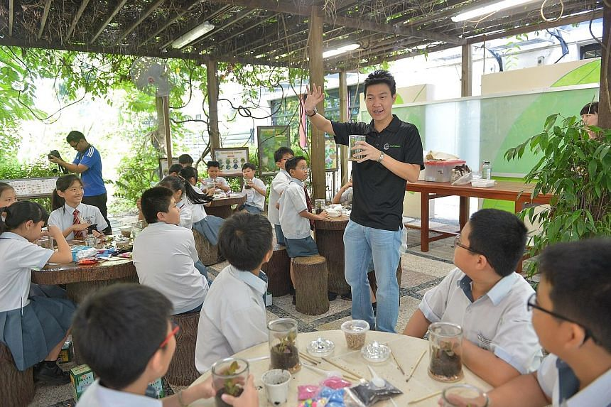 EcoPonics' Mr Ivan Sei conducting a lesson on terranium- making at Hougang Primary School. The primary school science curriculum now allows for pupils to have more room to understand and apply concepts.