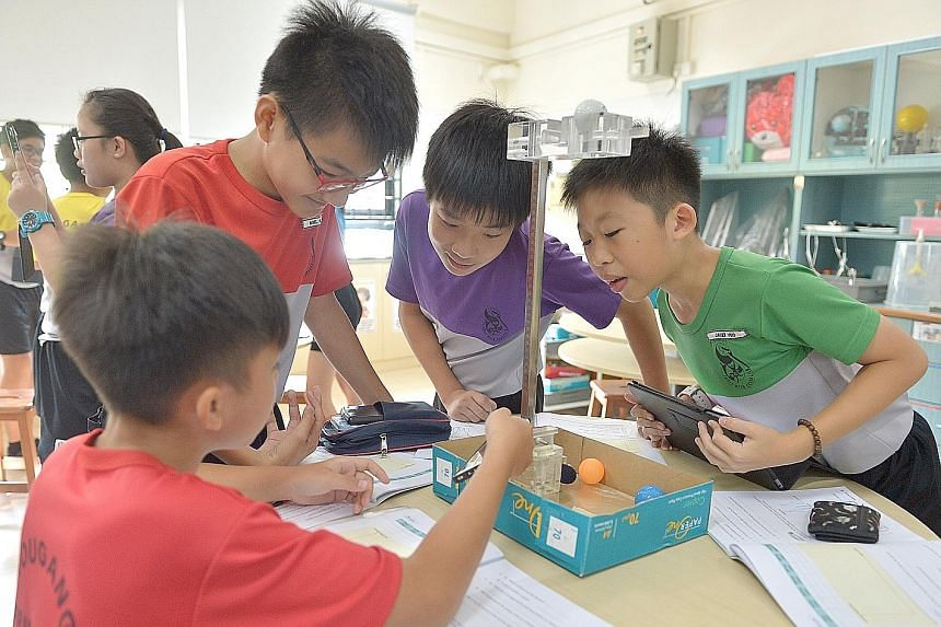 Hougang Primary pupils (from left) Neo Yong Jie, Noel Wong Jit Joon, Wayne Joo Jing Yao and Javier Yeo Kai Xiang conducting a science experiment on forces. Subjects from the sciences to the humanities have been refreshed by the Ministry of Education