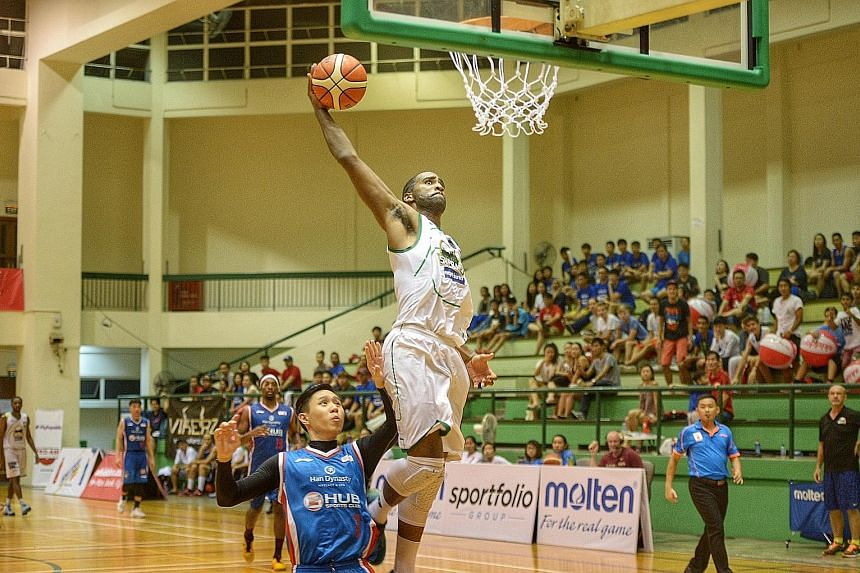Singapore Supras forward Jemell Swafford (white) attempts a dunk after escaping the attention of GHUB Basketball's Leonard Ong (blue) at the Pro-Am Singapore Basketball League play-off finals at the Delta Sports Hall yesterday evening. Supras won 78-