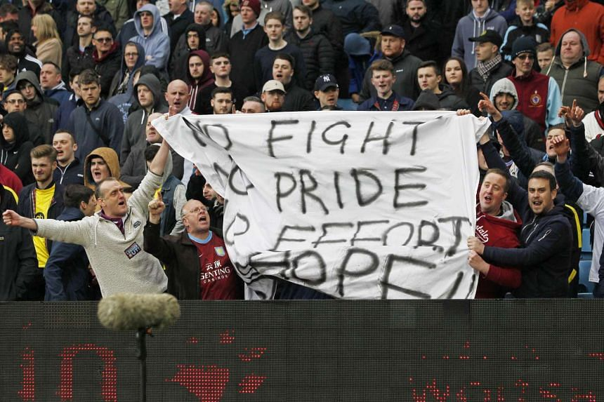 Aston Villa fans hold up a banner in protest against the team's poor performance.