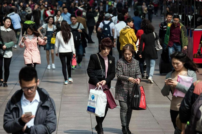 Two women carrying their shopping bags on a busy street in Shanghai on April 1, 2016.