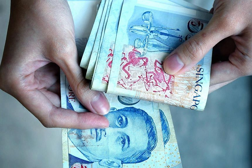 A woman holds a stack of $50 Singapore dollars.
