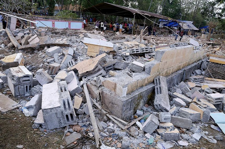 Indian officials and bystanders gather beside a collapsed building after a fire at the Puttingal Devi Temple in Paravur, on April 10, 2016.