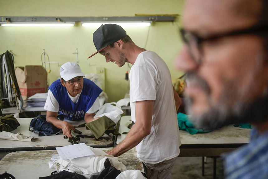 French designer Thomas Jacob (centre) working with inmates participating in his social project Pieta, at the San Pedro prision in Lima.