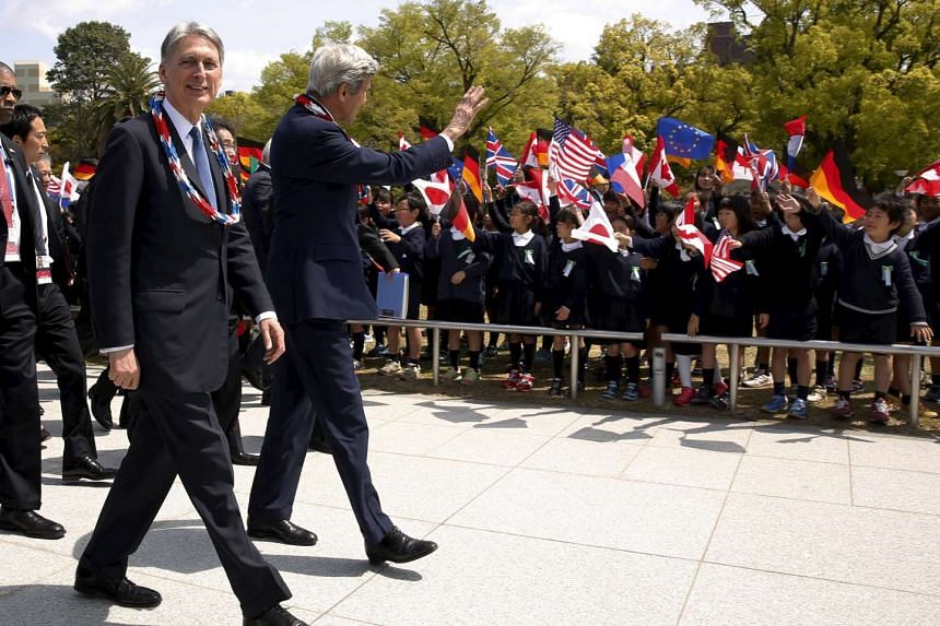 Britain's Foreign Minister Philip Hammond (left) and US Secretary of State John Kerry wave to schoolchildren.