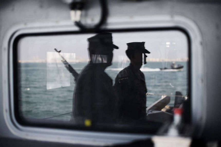 A reflection on the window showing US Navy sailors aboard a ship during the International Mine Countermeasure Exercise, on April 9, 2016.