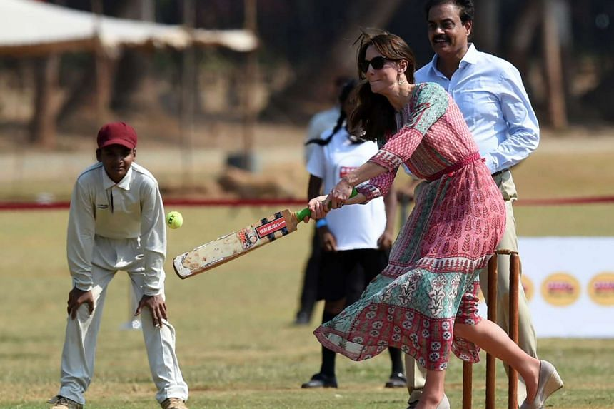Catherine, Duchess of Cambridge is watched by former Indian cricketer Dilip Vengsarkar (right) )as she plays cricket with Indian children in Mumbai on Sunday.