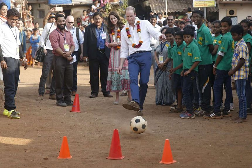 Britain's Prince William plays with a football as his wife Catherine watches during their visit to a slum in Mumbai on Sunday.