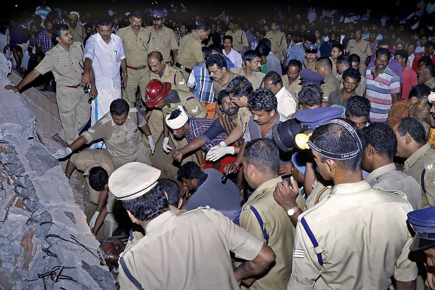 Officials and bystanders gathering beside a collapsed building amid efforts to rescue survivors after an explosion and fire at the Puttingal Temple in Paravur, in the South Indian state of Kerala, yesterday. Police said top officials of the temple ha