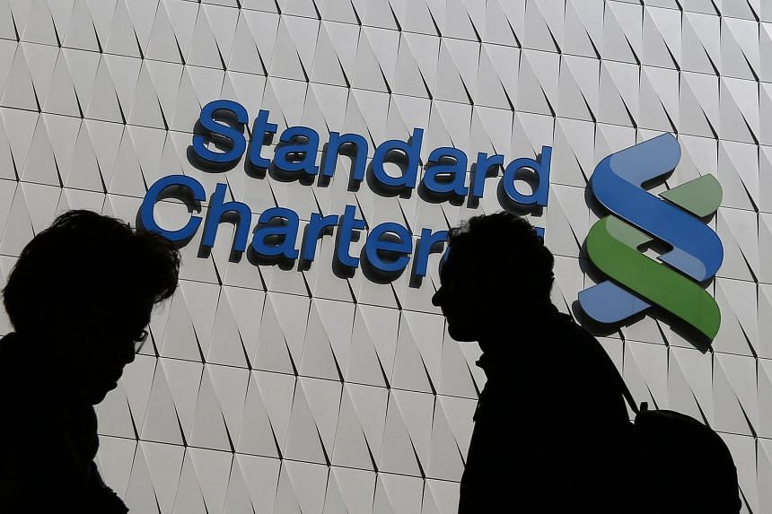 Passersby walk in front of the main branch of Standard Chartered in Hong Kong, in this Jan 8, 2015 file photo.