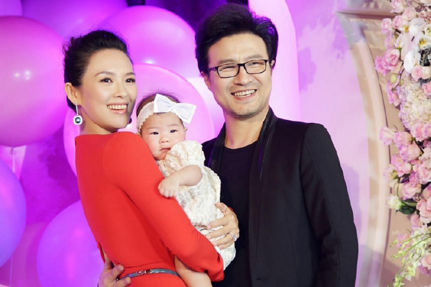 Actress Zhang Ziyi (left) with her baby daughter Xingxing (centre) and husband Wang Feng.