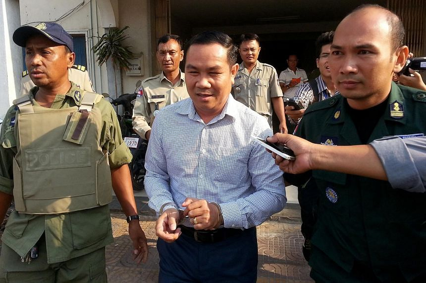 Cambodian opposition lawmaker Um Sam An (centre) being escorted by police officials in Phnom Penh.