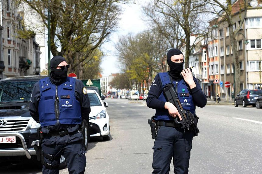 Belgian police officers stand guard in a street in Etterbeek, Belgium on April 9, 2016.