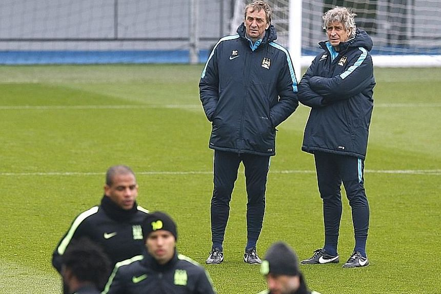 Manchester City manager Manuel Pellegrini (far right) and his assistant Ruben Cousillas watching over training as they prepare to face Paris Saint-Germain in their Champions League quarter-final, second-leg clash.