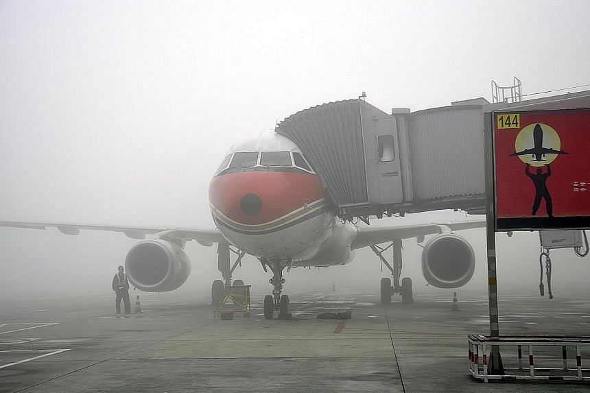 A plane in heavy fog at Shuangliu Airport in China's south-western city of Chengdu on Sunday. More than 10,000 passengers were stranded at the airport in the capital of China's Sichuan province due to the dense fog that prompted the authorities to is