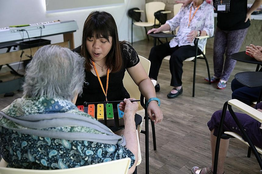 Music teacher Wan Hui Ling (left, in black) engaging a dementia patient on the xylophone as part of the music activities at the Montessori for Dementia Care centre in Upper Bukit Timah Road.