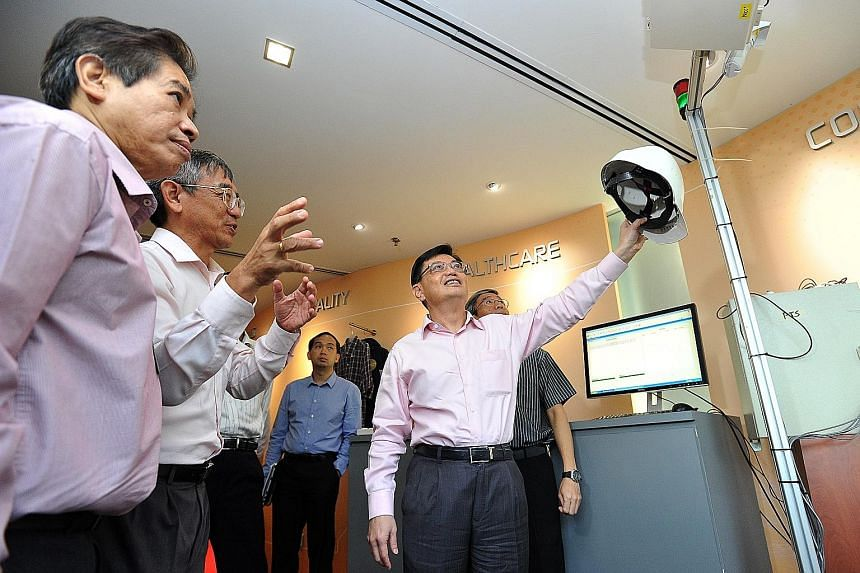 SIMTech executive director Lim Ser Yong (second from left) explaining the use of RFID-tagged helmets to Mr Heng during his visit yesterday. The RFID system was part of a project between SIMTech and the Land Transport Authority to track worker access