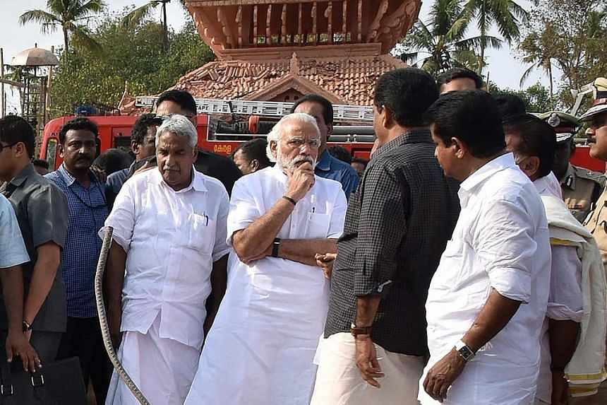 Indian Prime Minister Narendra Modi (centre) with Kerala Chief Minister Oommen Chandy (in white) beside him, at the site of the Puttingal Temple fire.