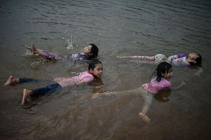 Children cooling off in a river in Temerloh, outside Kuala Lumpur, yesterday. Malaysia's Meteorological Department said the heatwave is expected to ease soon.