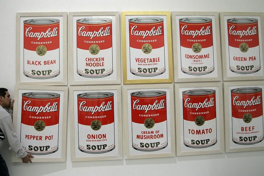 A worker hangs Campbell's soup, a print by artist Andy Warhol, before the opening of the exhibition Andy Warhol at Es Baluard museum in Palma de Mallorca.