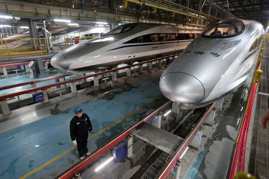 A Chinese worker standing beside China Railway High-speed trains at a high-speed train maintenance base in Wuhan, China.