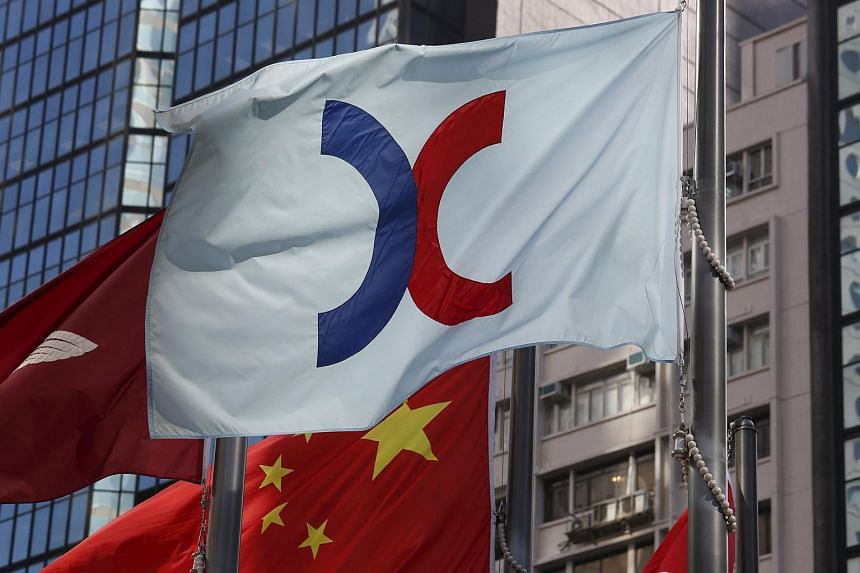 A flag of Hong Kong Exchanges and Clearing Ltd flies in front of a Chinese national flag.