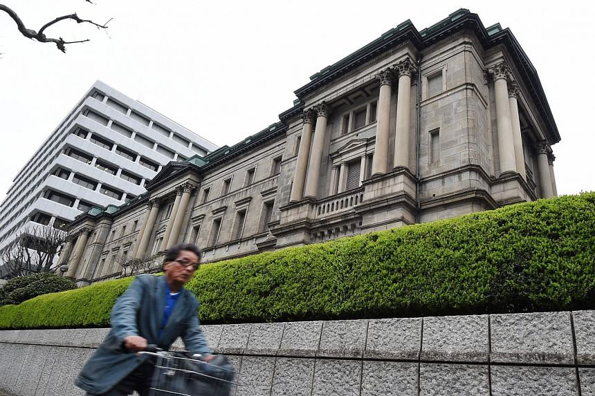 A cyclist rides past the headquarters of the Bank of Japan (BOJ) in Tokyo on April 1, 2016.