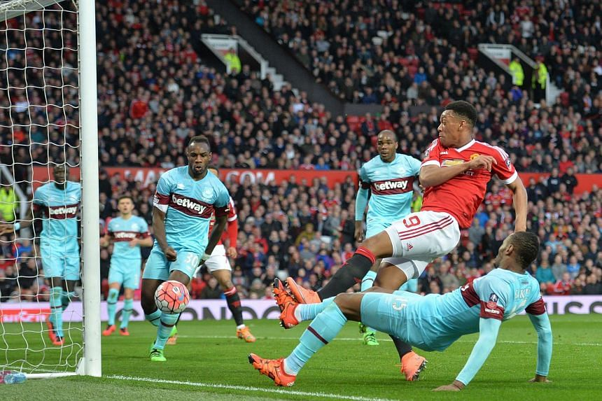 Manchester United's French striker Anthony Martial (in red) gets in front of West Ham United's Senegalese striker Diafra Sakho (right) to score a goal, on March 13, 2016.
