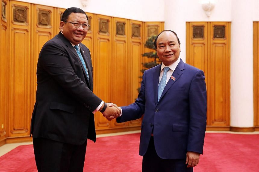 Vietnam's new Prime Minister Nguyen Xuan Phuc (right) shakes hands with Philippines' Foreign Minister Jose Rene Almendras in Hanoi, on April 11, 2016.