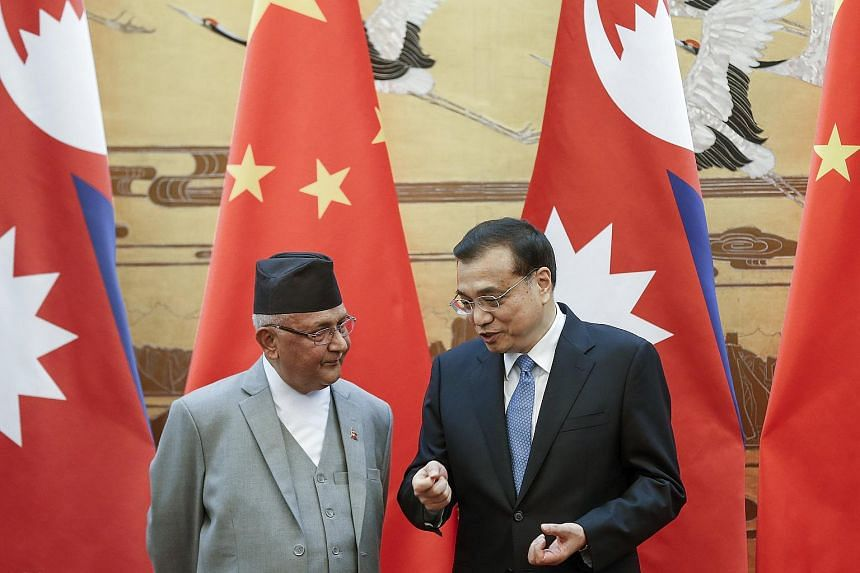 Chinese Premier Li Keqiang (right) talks to Nepal Prime Minister Khadga Prasad Sharma Oli during a signing ceremony in Beijing, China, on March 21, 2016.