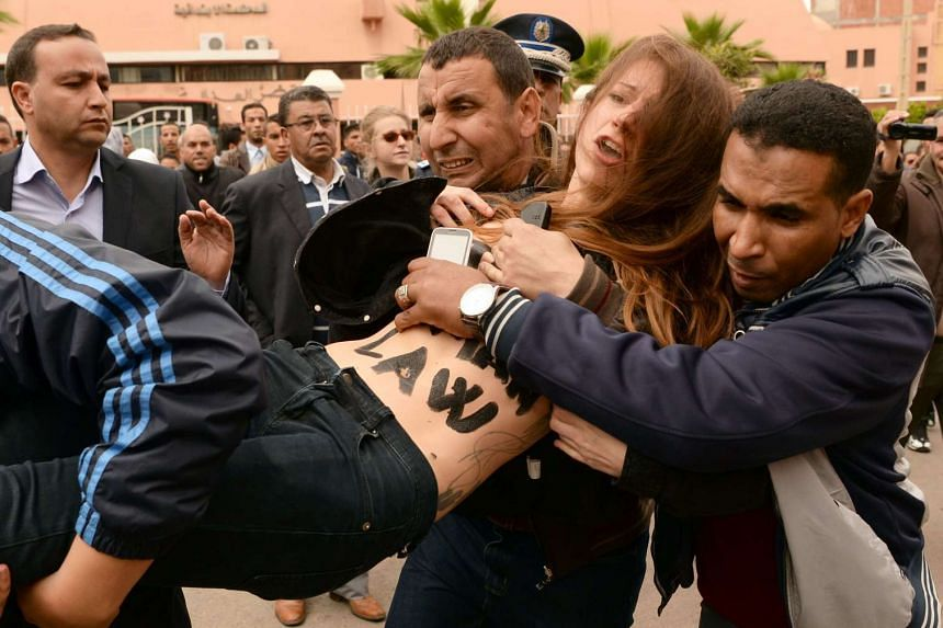 Undercover Moroccan police arrest a FEMEN activist as they demonstrated outside the court in Beni Mellal on Monday (April 11).