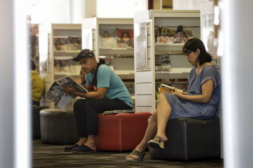 Adults reading books in Bishan Public Library on March 15, 2016.