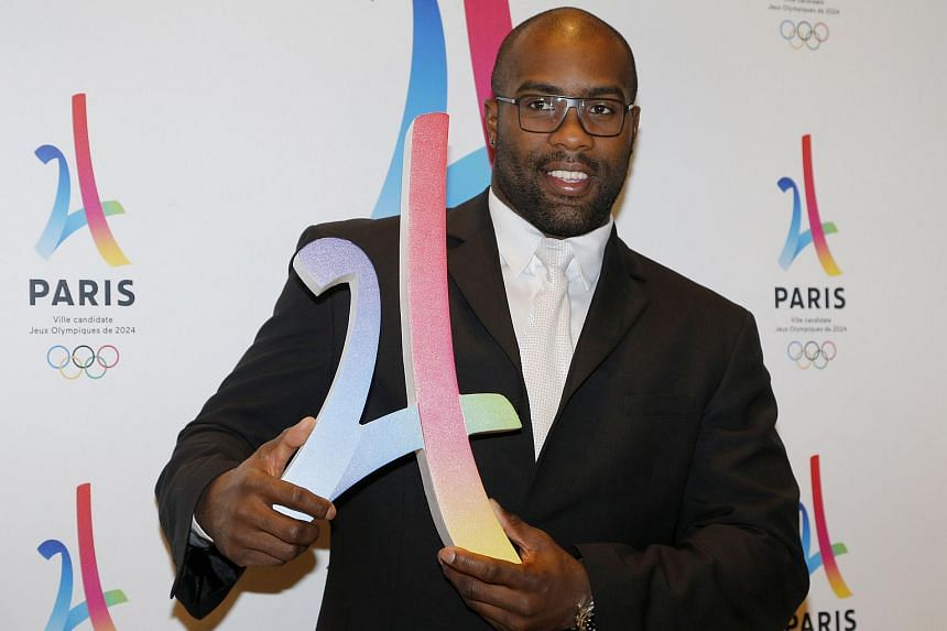 French judoka Teddy Riner poses with the logo of Paris as candidate for the 2024 Olympic summer games during a press conference in Paris.