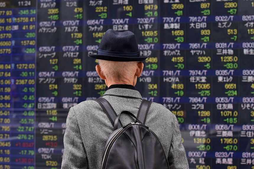 A pedestrian looks at a share prices board of the Tokyo Stock Exchange in Tokyo, on April 5, 2016.