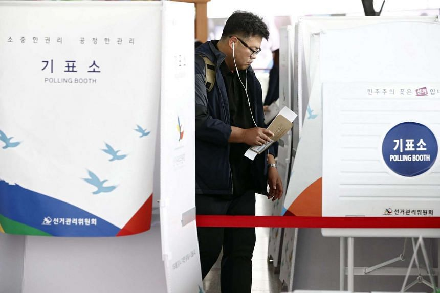 A South Korean man enters a polling booth to cast his vote at polling station in Seoul.