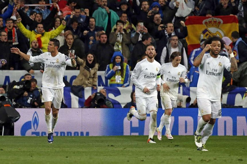 Real Madrid's Portuguese striker Cristiano Ronaldo (left) jubilates his third goal against Wolfsburg during the UEFA Champions League quarter final second leg match played at Santiago Bernabeu stadium in Madrid, Spain on April 12, 2016.