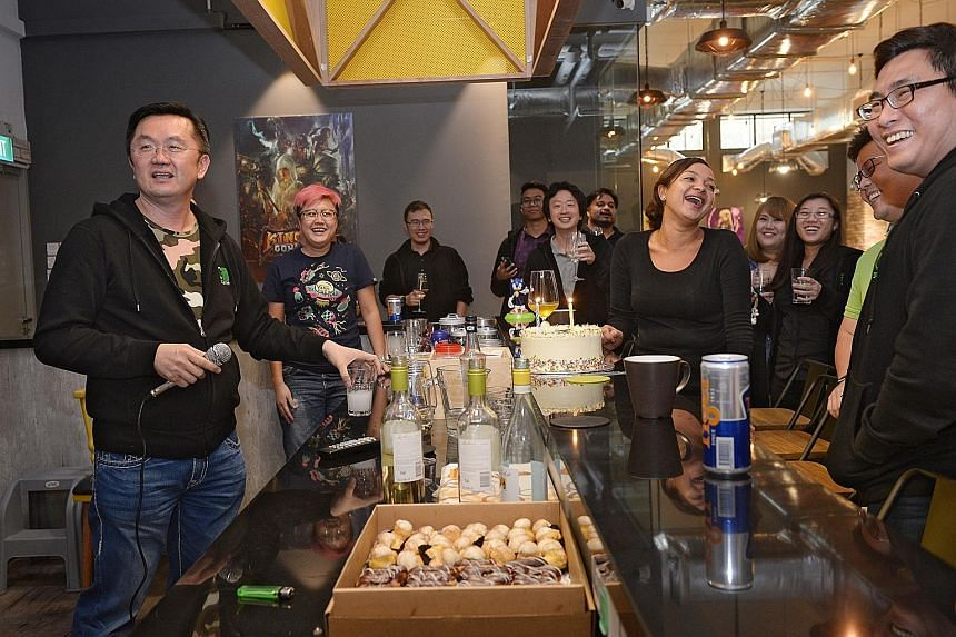 Founder and CEO of goGame David Ng (left) belting out a song on a karaoke machine during a birthday celebration for three of his employees at their Tai Seng Avenue office. The mobile game publisher's office has an industrial feel and a fully stocked