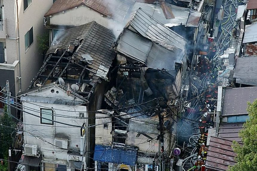 Firefighters assessing the damage from a fire yesterday in the densely packed Golden-gai district of Tokyo's Kabukicho entertainment area, known for its alleys packed with bars and eateries. The fire began around 1.20pm, according to the Tokyo Fire D