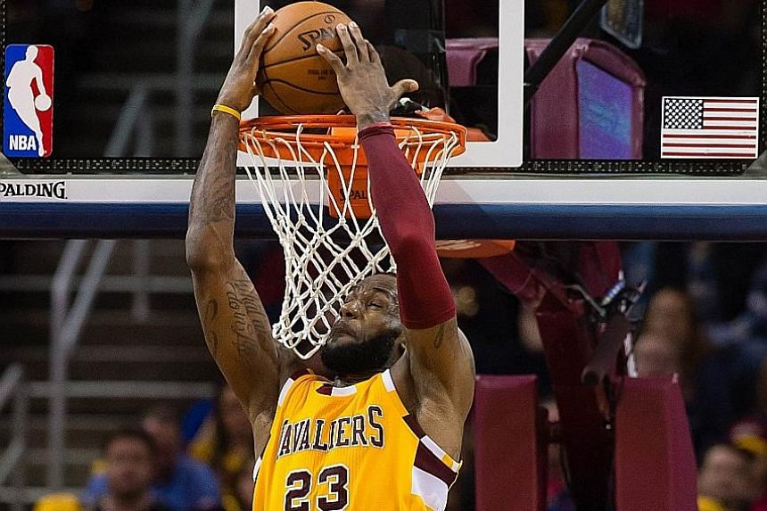 Cleveland Cavaliers forward LeBron James dunks over the Atlanta Hawks' Paul Millsap during the second half at the Quicken Loans Arena in Cleveland, Ohio. The Cavaliers won 109-94 to clinch top spot in the East.
