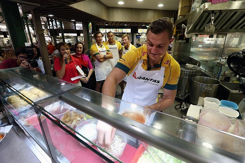 Australian sevens player Stephan van der Walt making a bowl of laksa at Lau Pa Sat, while team-mates (back, from left) Sam Myers, Frank Winterstein and Cameron Clark look on.