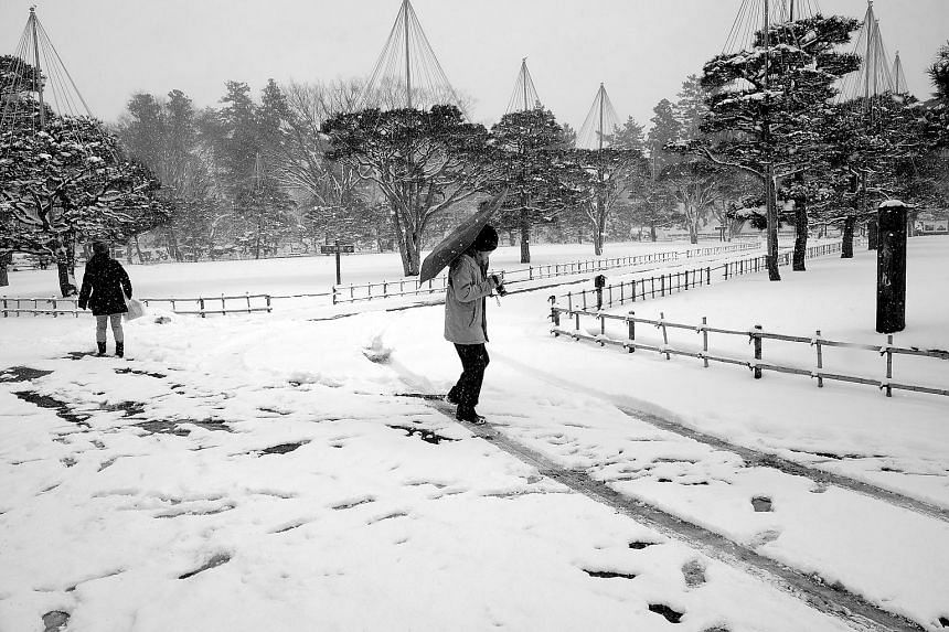 A man trying to hold on to his umbrella while fiddling with his camera as it snowed in Aizu, Japan (see Tip 2).