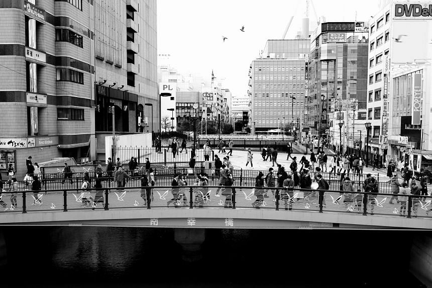 A panel of highly reflective glass with stylish lines on a building in Yokohama, Japan (see Tip 3). A bridge in downtown Yokohama, with birds flying overhead juxtaposed with the bird designs on the bridge (see Tip 4). A passer-by snapped looking at a