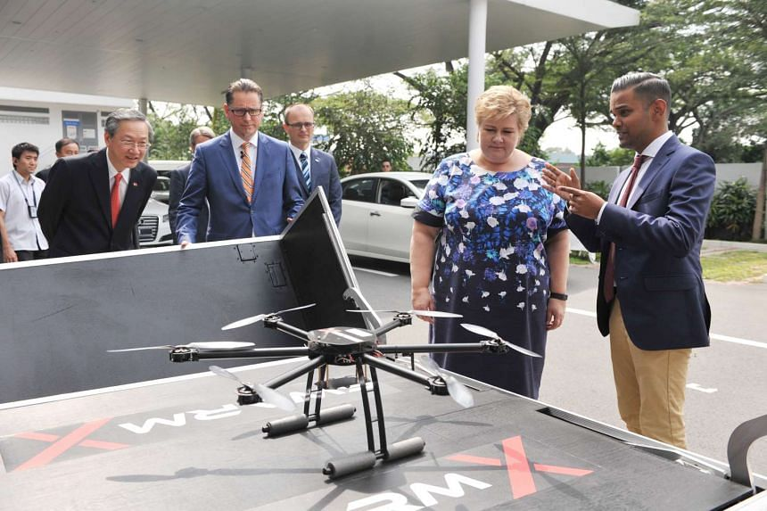 Mr Pulkit Jaiswal (right) explaining the drone docking system to Norwegian Prime Minister Erna Solberg (second from right), Mr Remi Eriksen (second from left) and Mr Sam Tan, Minister of State for Manpower (left).