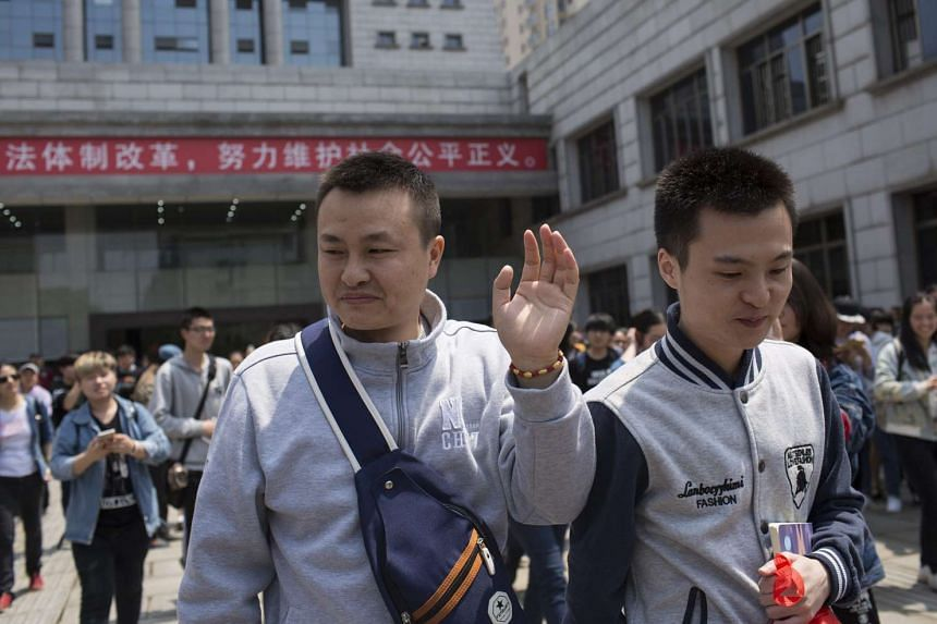 Sun Wenlin (right) and his partner Hu Mingliang (left) leaving a courthouse after the Changsha Furong District People's Court ruled against the couple, on April 13, 2016.